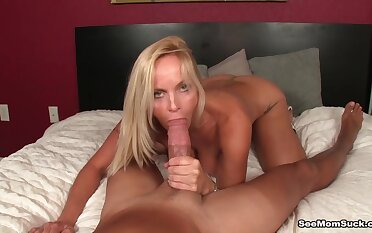 Naked MILF stands nude with an increment of throats a generous cock while being taped